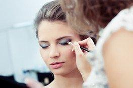 Visagistin trägt Make-up auf