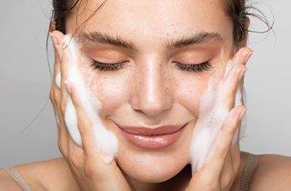 Frau reinigt Gesicht