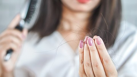 Frau bürstet ihre Haare