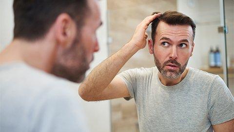 Mann sieht in den Spiegel.