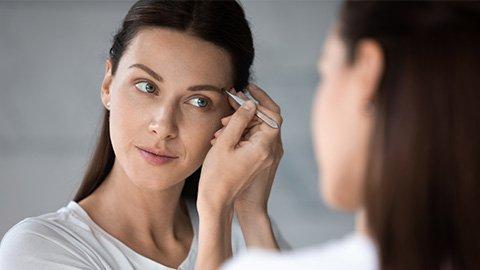 Frau zupf die Augenbrauen