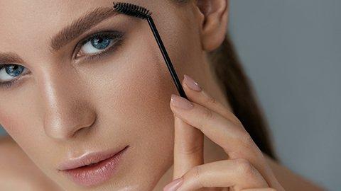 Frau schminkt Augenbrauen