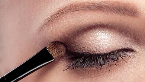 Frau schminkt Augenlid mit Pinsel