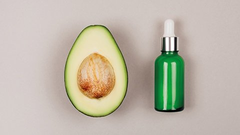 halbe Avocado und Pflegeöl