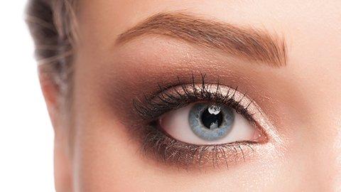 Frau mit blauen Augen und Kupfer Lidschatten