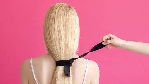 Blonde glatte Haare sind mit schwarzem Haarband zusammen gebunden