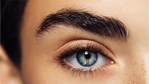 Blaues Auge mit buschigen Augenbrauen