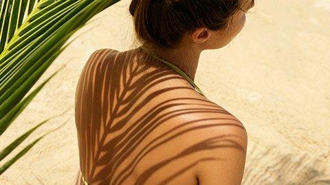 Frau unter Palmenblatt