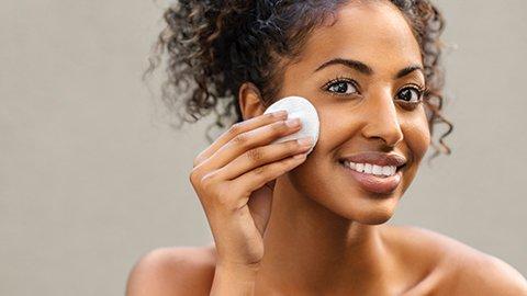 Frau reinigt Gesicht mit Toner