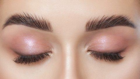 Frau mit geschlossenen Augen und rosa Lidschatten