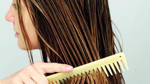 Frau kämmt nasse Haare