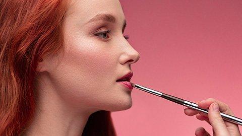 Frau schminkt Lippen
