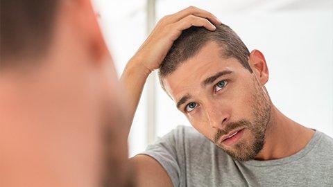 Mann mit kurz rasierten Haaren schaut sich im Spiegel an