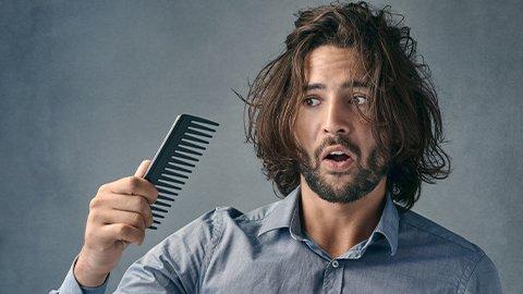 Ein Mann kämmt seine offenen langen Haare mit Locken