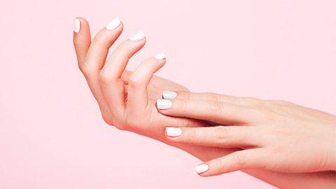 Weiße Fingernägel vor Rosa Hintergrund