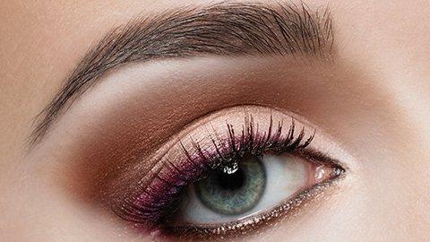 Grünes Auge mit pinkem Lidstrich und goldenem Lidschatten