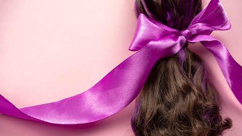 Dunkelbrauner Zopf mit Haarschleife in lila