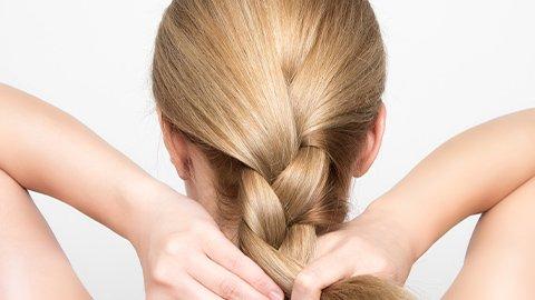 Frau mit blonden Haaren flechtet sich selbst die Haare
