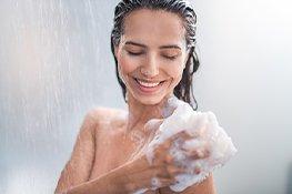 Frau wäscht ihren Körper unter der Dusche mit Duschschaum