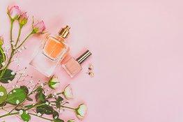 Parfum Flakon und Nagelack auf rosa Hintergrund