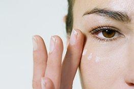 Frau trägt unter dem Auge Gesichtscreme auf