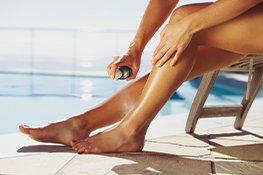 Beine mit Sonnenschutz einsprühen