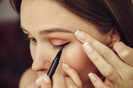 Frau zieht Eyeliner