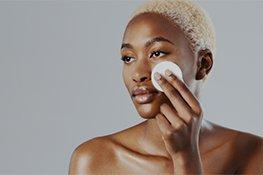 Frau entfernt Make-Up vom Gesicht mit Wattepad und Make-Up Entferner