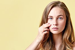 Frau trägt getönte Gesichtscreme auf