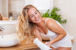 Frau föhnt ihre Haare in einem Bad