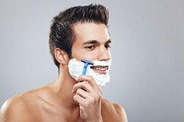 Mann verwendet Rasiercreme und rasiert sich