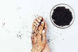 Hände verwenden schwarzes feinkörniges Handpeeling