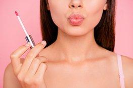 Frau hält Lipgloss in der Hand