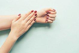 Zwei weibliche Hände mit rot lackierten Nägeln